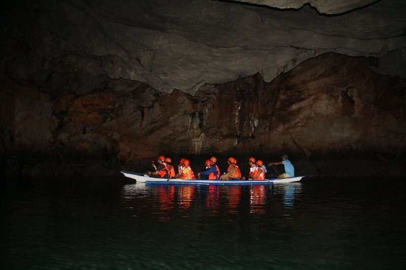 Turisti sulla canoa che naviga il fiume sotterraneo di Puerto Princesa a Palawan nelle Filippine