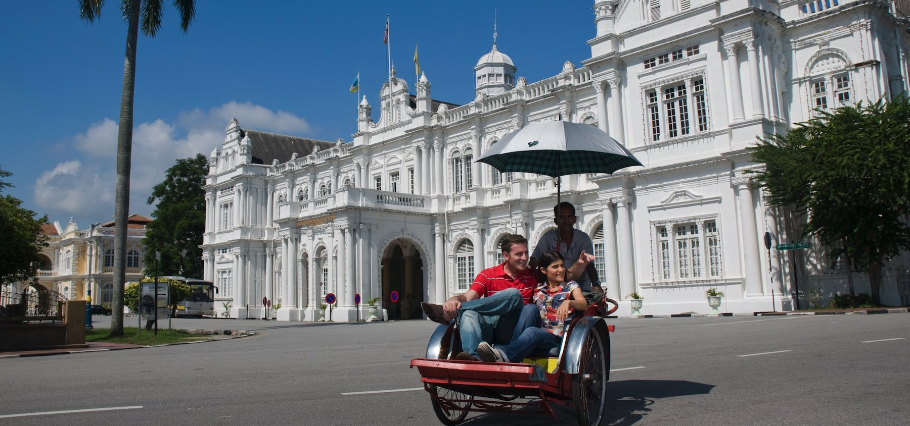 Turisti in Trishaw per le strade di Penang, Malesia
