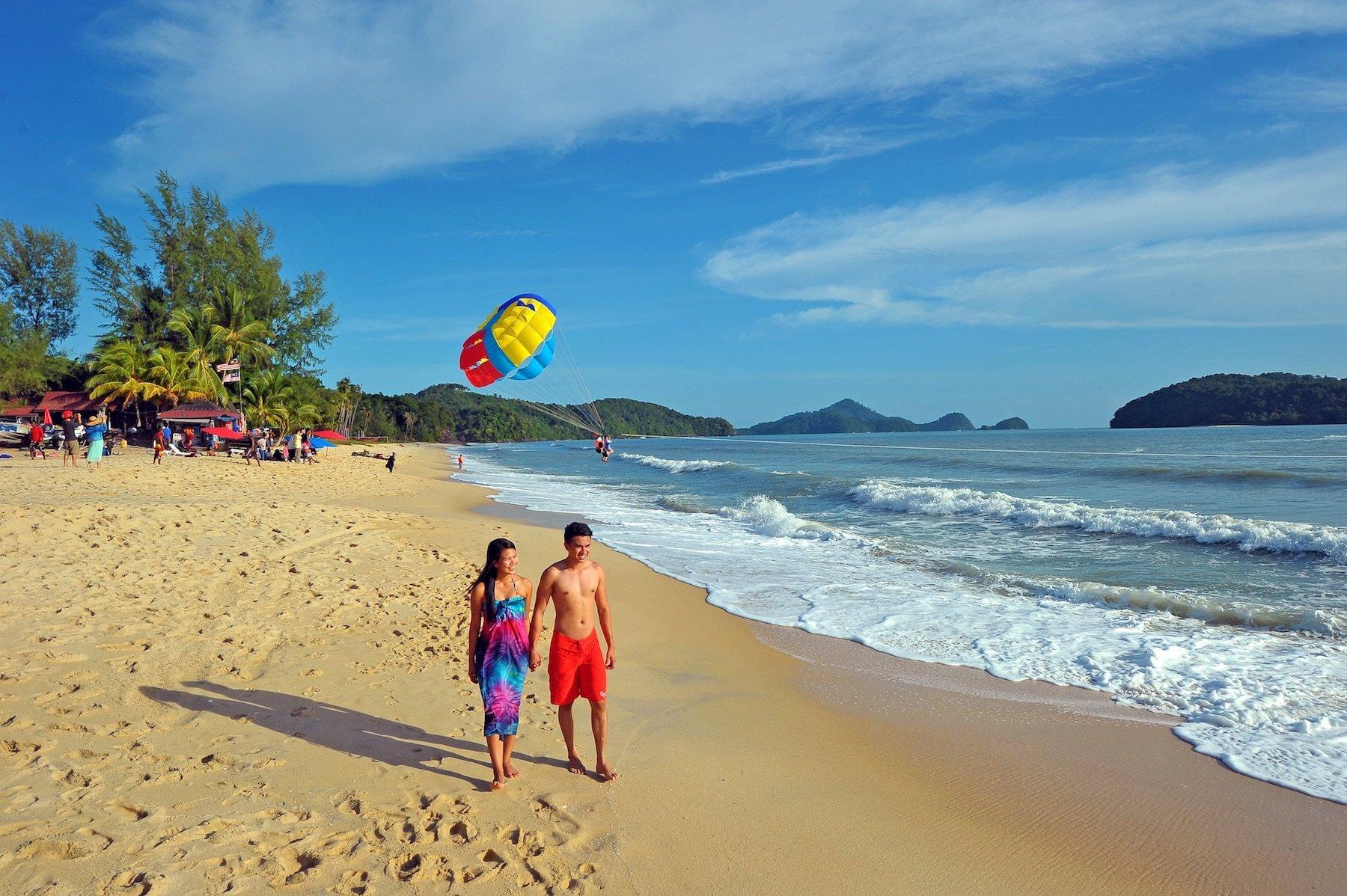Turisti che passeggiano lungo la spiaggia Cenang a Langkawi