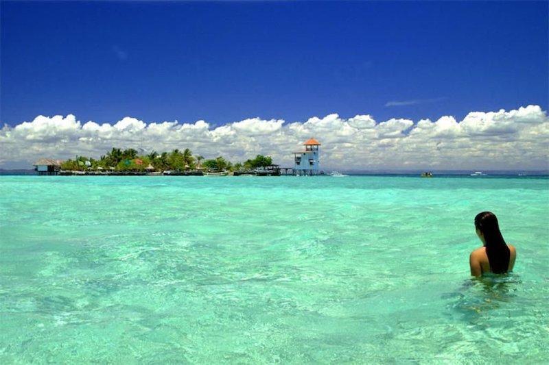 Turista nel mare davanti all'isola di Nalusuan nel santuario marino di Cebu