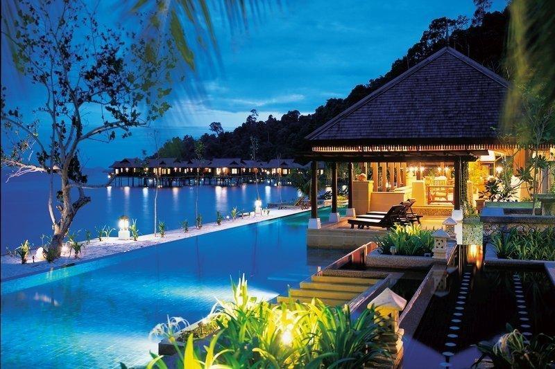 Scenario notturno con Piscina e bungalow su palafitte a Pangkor Laut, Malesia