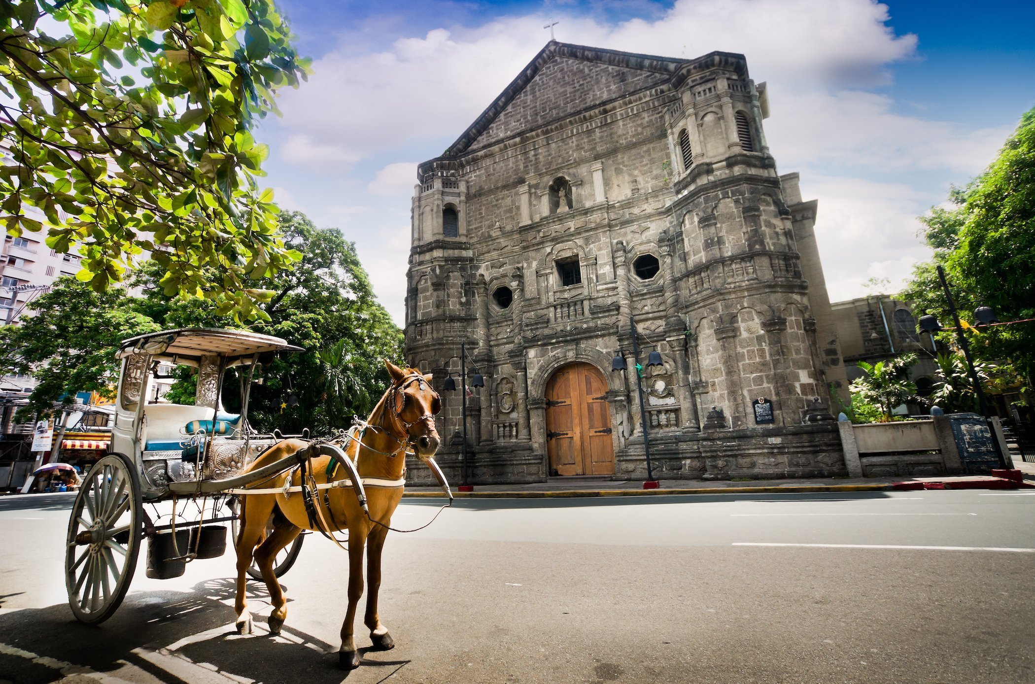 Calesse davanti la chiesa di Manila nel quartiere di Intramuros