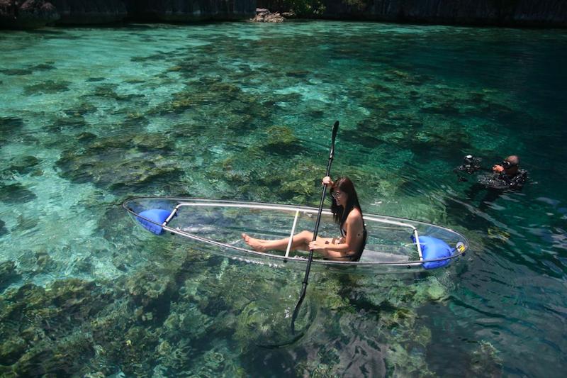 Turista a bordo di un kayak trasparente al Two Seasons Coron Island Resort & Spa, Palawan